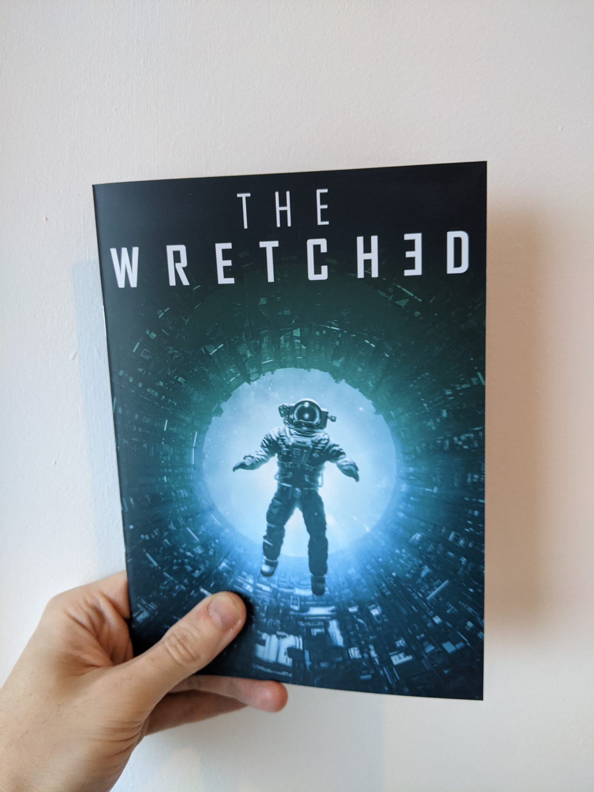 "A hand holds an A5 zine against a white background. The title on the zine reads ""The Wretched"". On the cover, a silhouette of an astronaut falls backwards into a glowing green and blue void in the middle of a maze of industrial pipework."