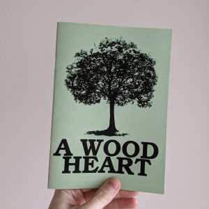 A hand holds a green zine against a white wall. The cover shows an illustration of a large tree, and the words A WOOD HEART beneath it.